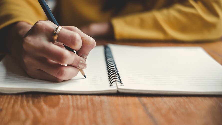 woman writing resume notes in a notebook