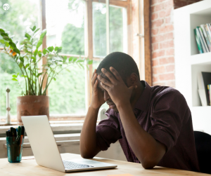 African American man holding his head disappointed sitting at a desk