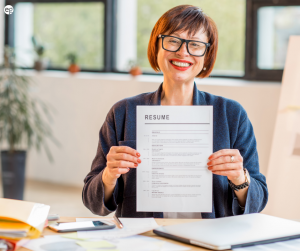 Older AAPI woman proudly holding up her resume surrounded by papers and folders on a desk