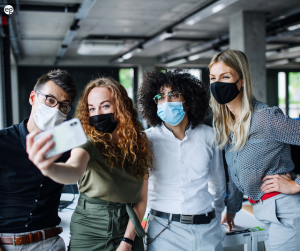Masked coworkers taking a selfie