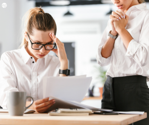 Two women looking nervously at paperwork