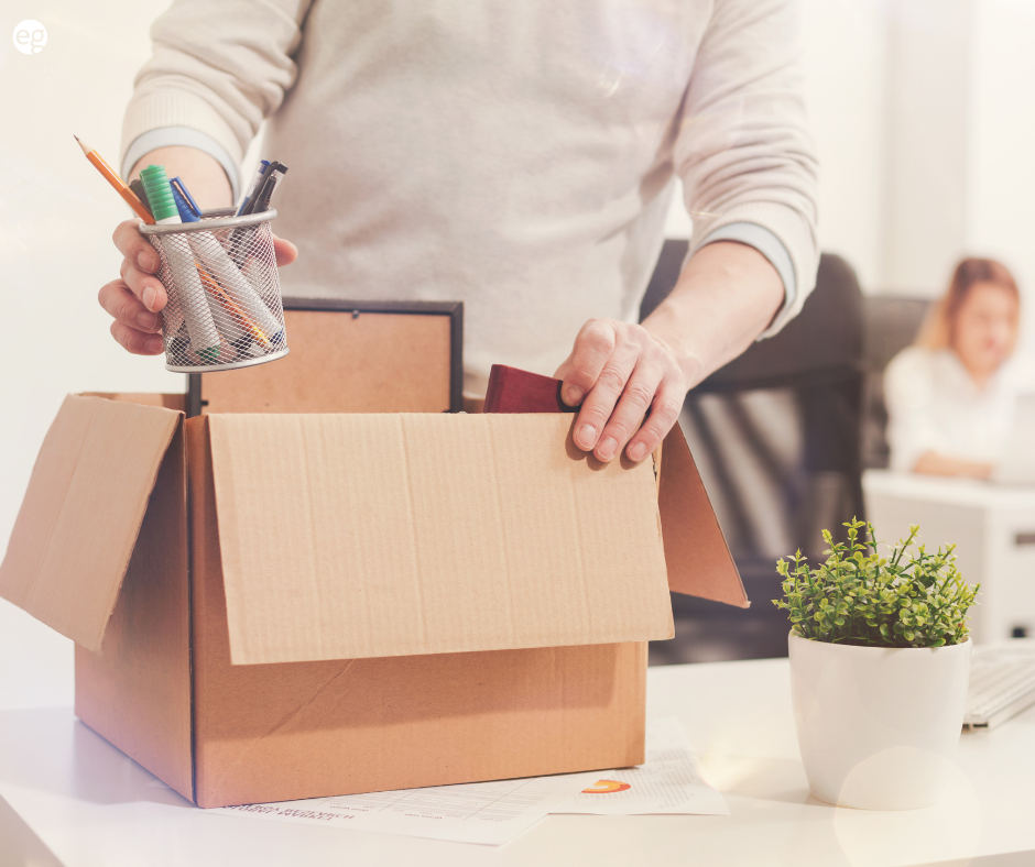 Person packing up a cardboard box with work items in resignation