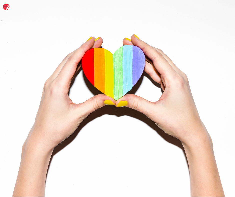 Hands holding a pride rainbow heart
