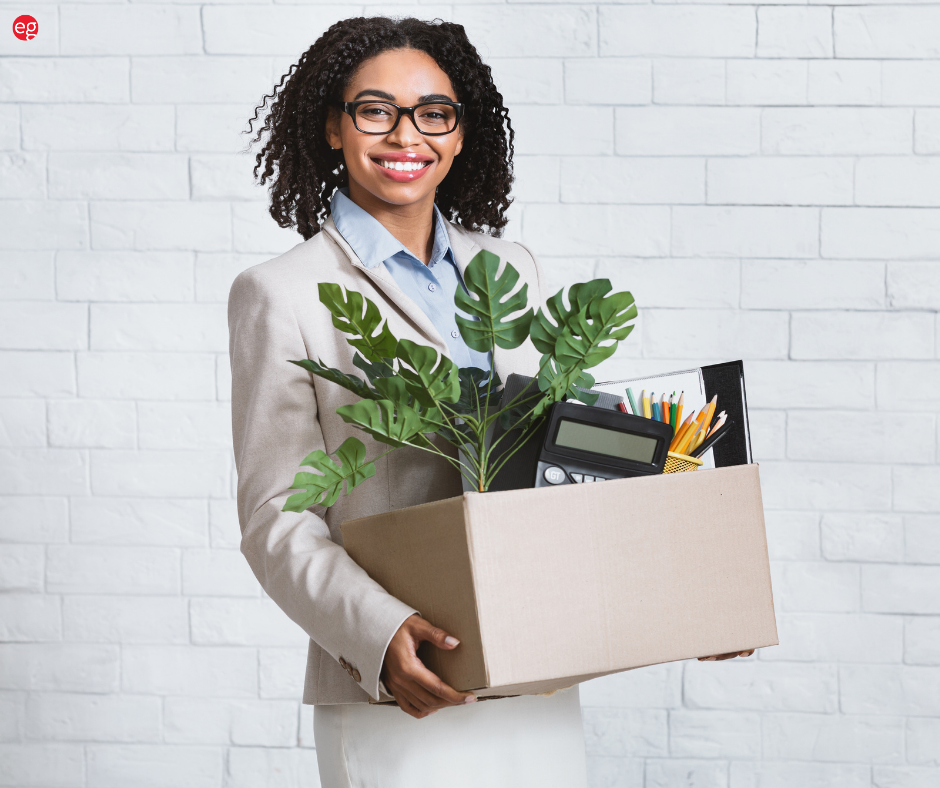 BIPOC Woman Smiling Holding a Box of Office Items