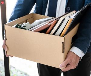White man holding a cardboard box of books