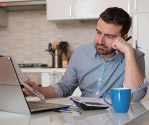 White man looking stressed with a laptop and papers
