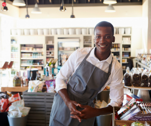 Black man in an apron leaning on a store shelf