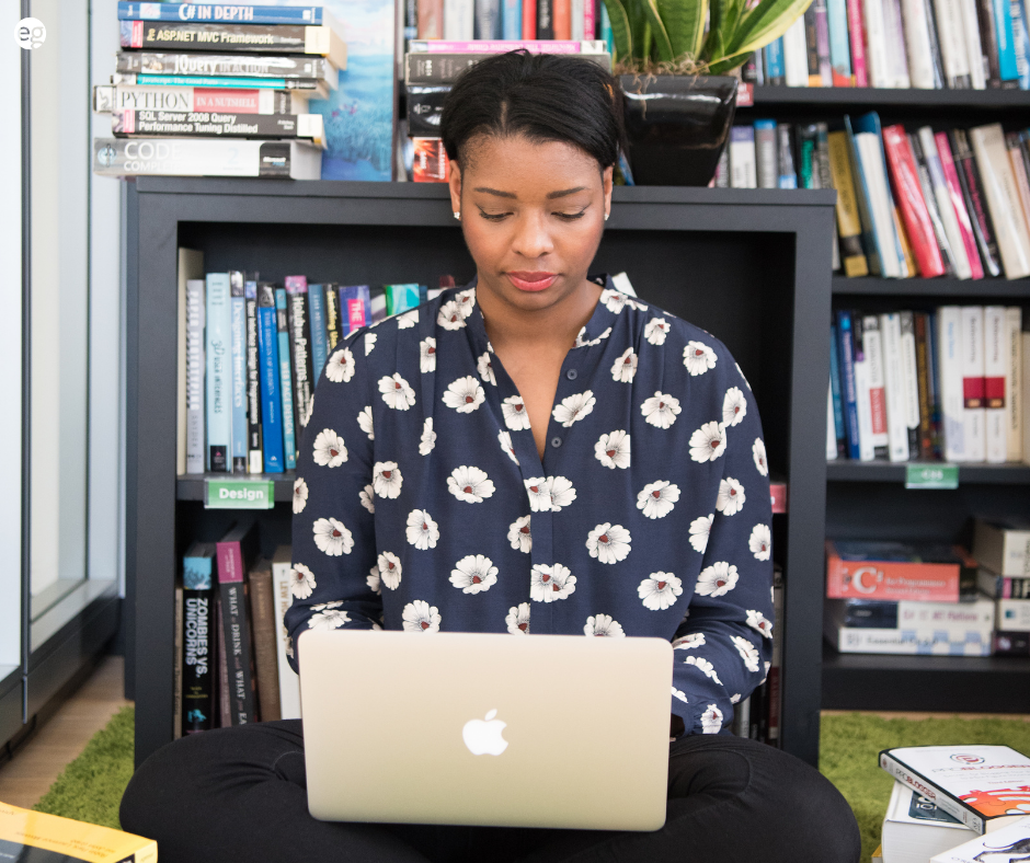 African American woman using a laptop surrounded by books