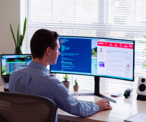 Man working from home on multiple screens