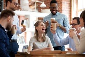 Happy diverse colleagues celebrate during a break in office
